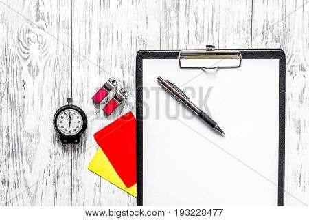 Referee preparing to competition. Yellow and red cards, stopwatch, whistle on wooden background top view.