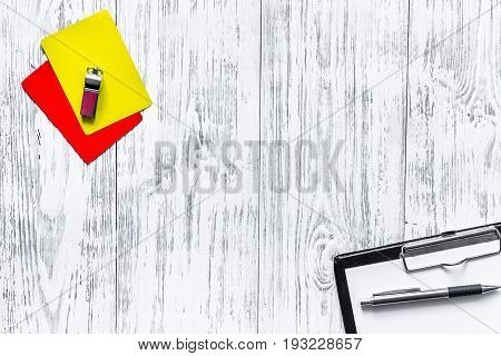 Referee tools. Yellow and red cards, whistle on wooden background top view copyspace.