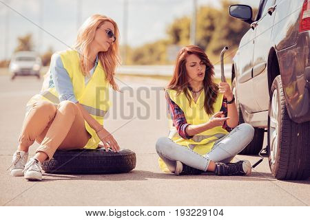 Two girls on the road trying to fix their car.Changing tire on broken car on road.