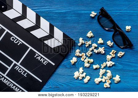 Watching the film. Movie clapperboard, sunglasses and popcorn on blue wooden table background top view.