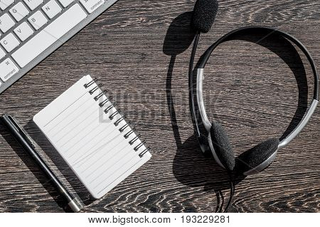 operator headset, notebook and keyboard for contact us feed back on call center work desk stone background top view mockup