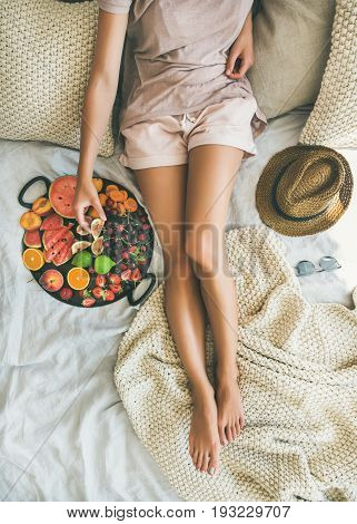 Summer healthy raw vegan clean eating breakfast in bed concept. Young girl wearing pastel colored home clothes taking fruit from tray full of fresh seasonal fruit. Top view