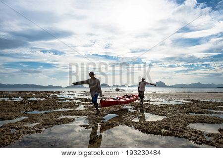 EL NIDO, PALAWAN, PHILIPPINES - MARCH 29, 2017: Horizontal view of two men carrying a kayak from the water to the beach at Las Cabanas Beach.