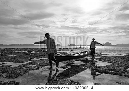 EL NIDO, PALAWAN, PHILIPPINES - MARCH 29, 2017: Black and white picture of two men carrying a kayak from the water to the beach at Las Cabanas Beach.