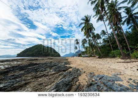 EL NIDO, PALAWAN, PHILIPPINES - MARCH 29, 2017: The Beach of Las Cabanas full of rocks, sand and coconut trees.