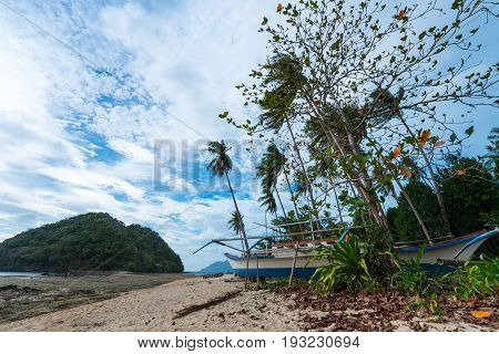 EL NIDO, PALAWAN, PHILIPPINES - MARCH 29, 2017: Wide angle view of a boat in the sand at Las Cabanas Beach.