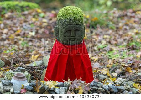 KYOTO JAPAN - 19 NOVEMBER 2015: Stone statues and red hood in the garden at Sanzenin Temple in Kyoto Japan