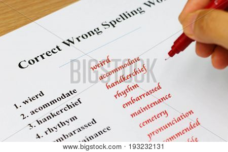 English spelling sheet on table with hand holding red pen