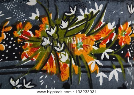 Knitwear fabric with floral colorful abstract pattern of blue, green and orange flowers and leaves.