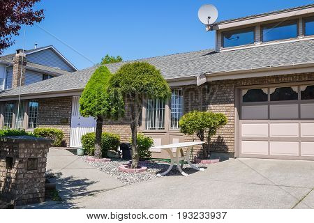 Front yard of family house with decorative trees in front. Entrance of a house garage door beside and concrete driveway in front