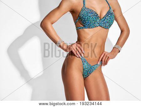 Close up photo of fit healthy muscular female body on light grey background with shadow