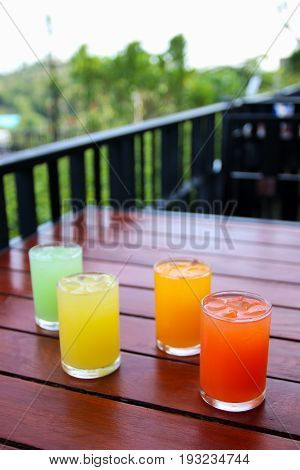 Refreshing drink of cold Juice  (pineapple, orange, punch, guava) on wood table.