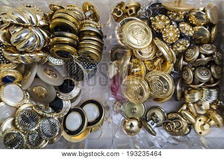 Close up of a collection of gold, silver and metal antique vintage buttons with different patterns in plastic containers in an sewing studio.
