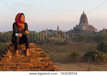 Woman sitting on temple bricks meditating at sunset over the Bagan plain in Myanmar