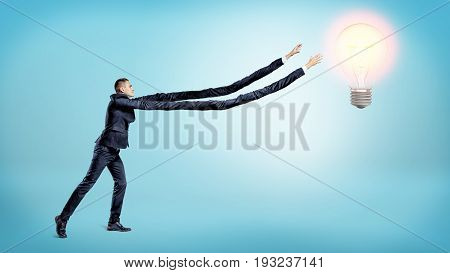A tiny businessman trying to reach a glowing bulb with his unnaturally elongated arms. Reach your dream. Innovation in business. Big effort for success.