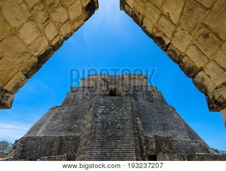 Unique triangular perspective of stone Mayan pyramid from ancient  archway at Uxmal Ruins, Merida, Mexico.