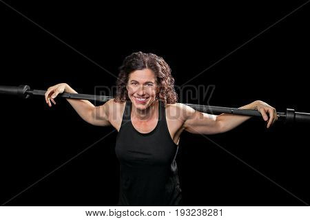 A female weight lifter relaxes with arms stretched out over a barbell that is across her shoulders. She smiles for the camera and is cross lit on a black background.