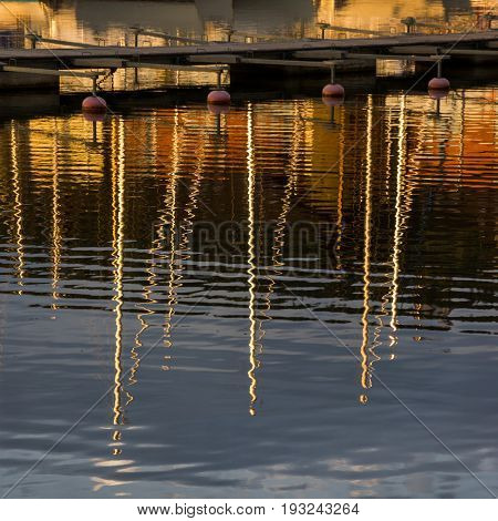 Water reflections at sunset. Masts of yachts reflected in blue water. Abstract colorful background.