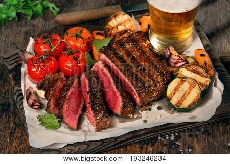 Sliced rare grilled steak on rustic cutting board with set of grilled vegetables on dark wooden rustic table with lager beer close up