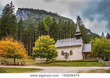 Church on the Alpine lake Lago di Braies. The concept of walking and eco-tourism. Travel to the Southern Tyrol, Italy