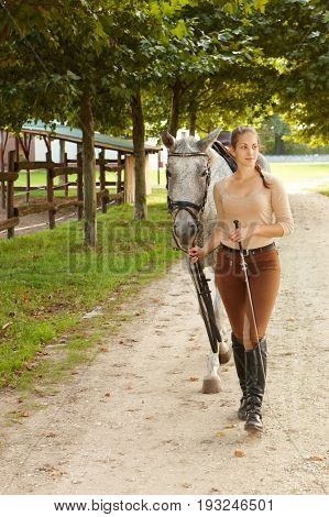 Young woman leading horse on leading-rein outdoors. Full size.