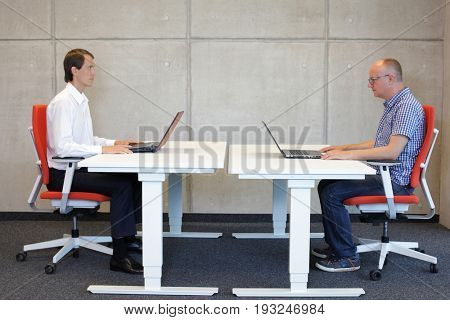 two men coworking  on chairs in office,one fit in correct sitting posture observing the other crooked one