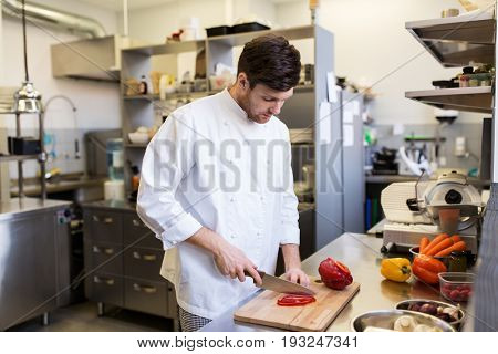 cooking food, profession and people concept - happy male chef cook with knife chopping paprika on cutting board at restaurant kitchen