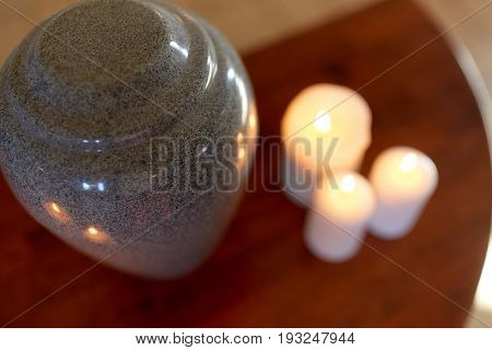 funeral, cremation and mourning concept - funerary urn and candles burning on table