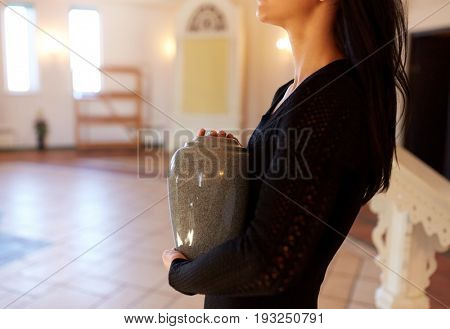 cremation, people and mourning concept - close up of woman with cinerary urn at funeral in church