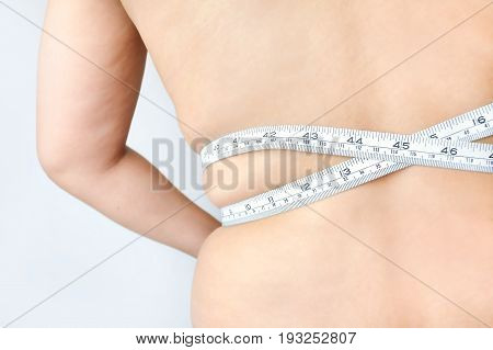 Woman measuring her waistline, isolated on a white background