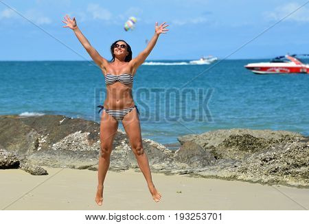 Tourist Woman Play And Jumping On The  Beach