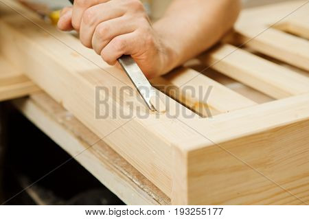Man working with carving equipment in workshop. Manual making of chinseling groove in wooden bar, worker carpenter hands holding chisel