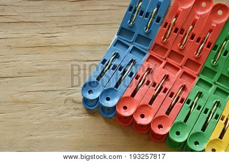 colorful plastic clothes peg clipping hard white paper on wooden board