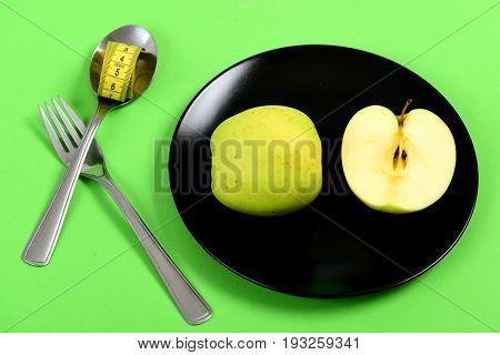 Apple Halves Set Lying On Black Ceramic Plate Near Cutlery
