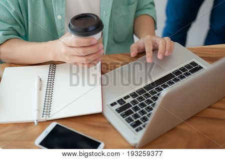 Asian hipster male with casual cloths using laptop computer touchpad while drinking coffee in cafe on workday. Freelance worker lifestyle and activity concept