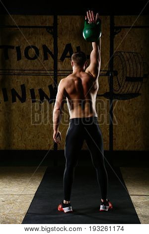 Rear View Of Man Exercising With Weights