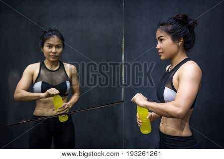 Young Asian athlete woman drinking sport drink or energy drink after exercise in fitness gym healthy lifestyle concepts