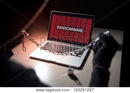 Male hacker locking computer by using chain and padlock malware ransomware Trojan concept. Internet security concept