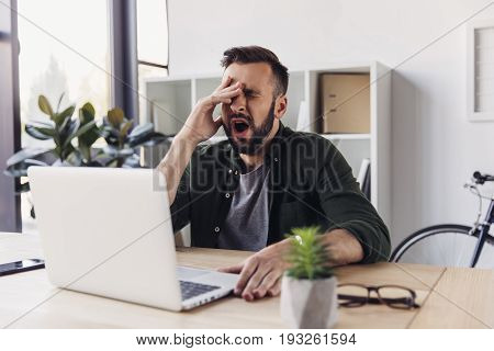 Tired Young Businessman Using Laptop And Yawning In Office