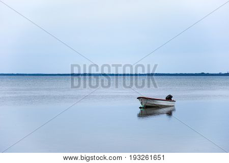Single small boat with reflection in a calm water