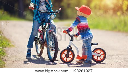 children riding on a bicycles at gravel road in the park in summer. Older and younger brothers on bikes