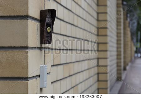 The button on the intercom mounted on the brick wall