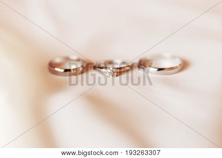Set of three golden rings on silk textile - engagement ring with diamond and pair of wedding rings. Symbol of love and marriage.