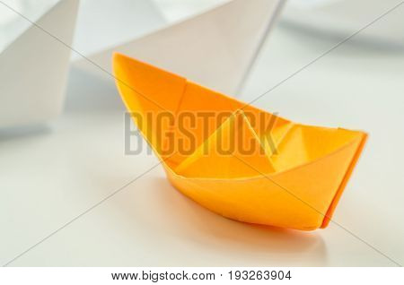 leader paper ship followed by other origami ships