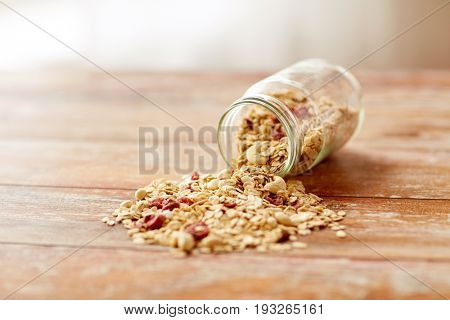food, healthy eating and diet concept - jar with granola or muesli poured on wooden table