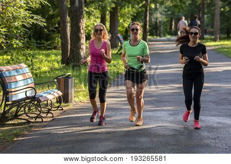 Group of adult pretty fit women jogging in park together.