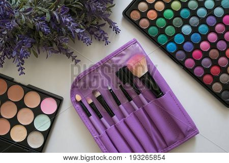Glamour feminine cosmetic background in natural colour. Cosmetic objects frame with brushes, lavender flowers, eye shadows, perfume bottle, lipstick, cream. Getting ready for a party