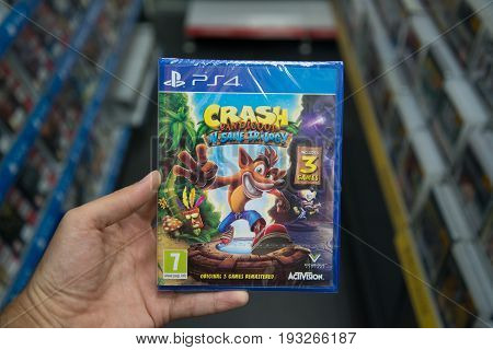 Bratislava, Slovakia, june 30, 2017: Man holding Crash Bandicoot N Sane Trilogy videogame on Sony Playstation 4 console in game store