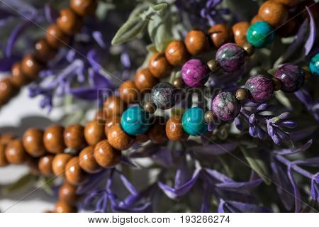 Beautiful wooden beads with gemstones chrysocolla, tourmaline and turquoise on flowers background. Mala beads. rosary for meditation