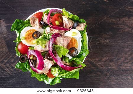 An overhead photo of a plate of salad with canned tuna, boiled eggs, green lettuce leaves, purple onions, black olives, and red cherry tomatoes, on a dark rustic texture with a place for text